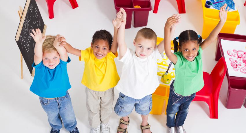 Four young children at school raising their hands together