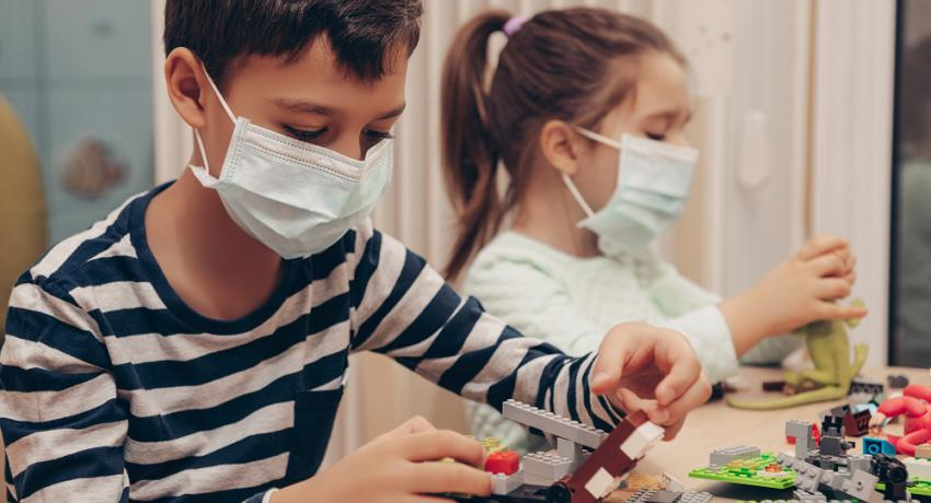 Children playing with Legos while wearing face masks.