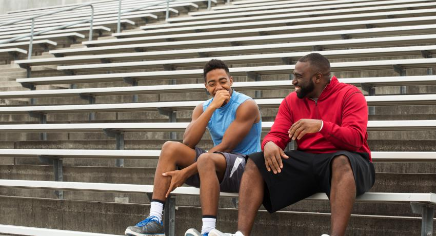 A teenager and his mentor or coach sit on bleachers in a stadium talking and smiling.