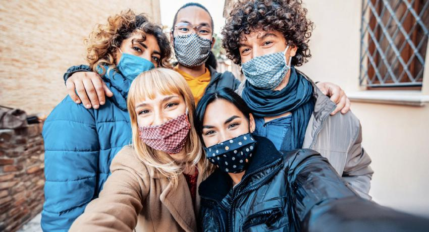 Youth wearing face masks gather for a selfie.