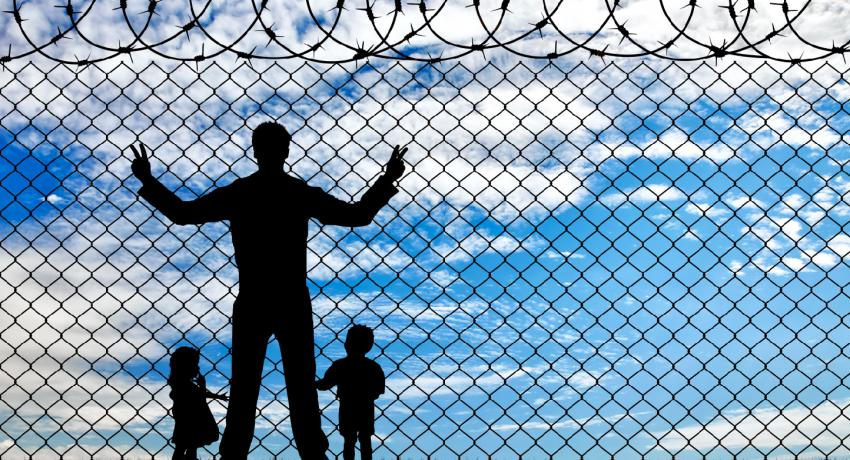 adult in prison with children near fence